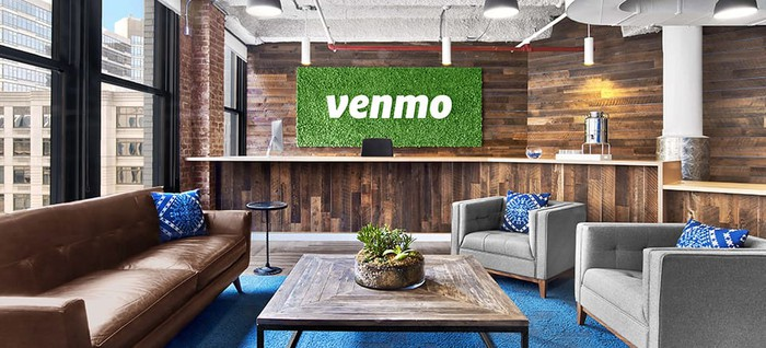 """Interior of contemporary office with large """"Venmo"""" signage in entrance lounge."""