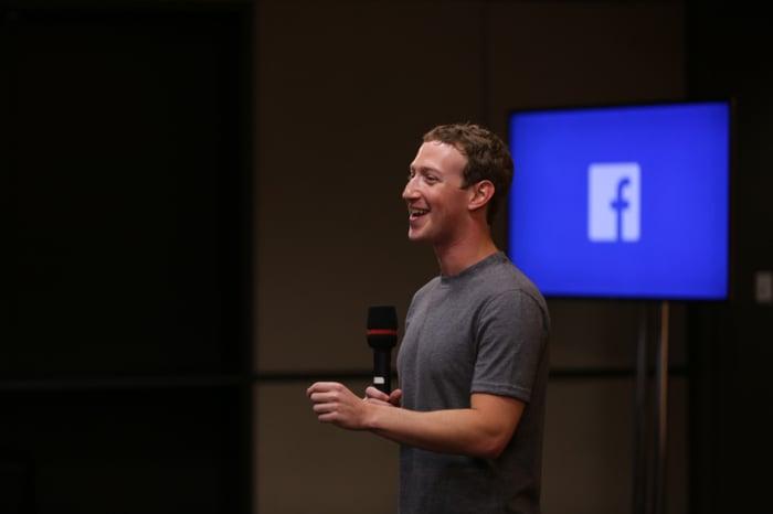 Mark Zuckerberg standing, holding a microphone.