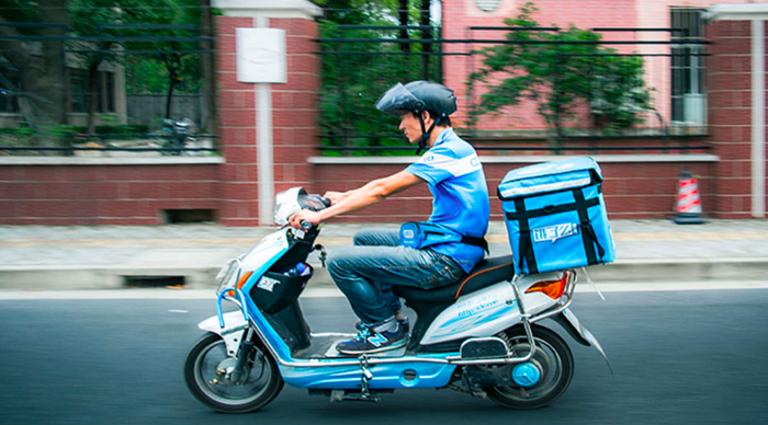 An Ele.me delivery employee is seen riding a scooter through the streets.