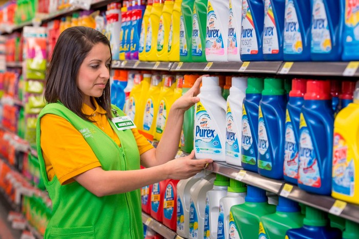 A Walmart employee stocks shelves with detergent.