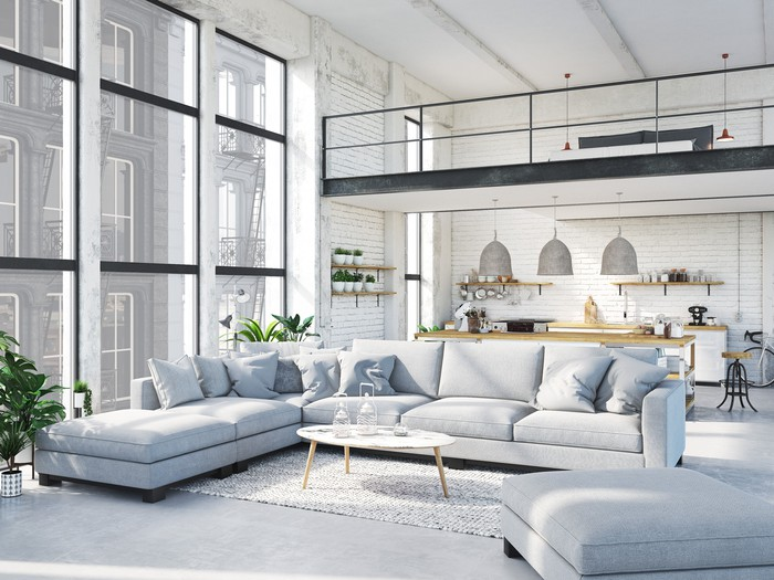 A large, brightly lit apartment with a seating arrangement of sofas.