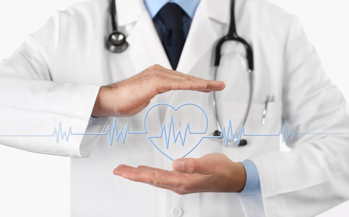 Doctor holding hands over hearbeat monitor icon