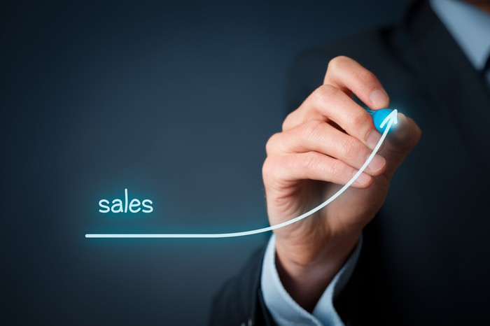 "A person in a suit drawing an upward-trending curve with the word ""sales"" displayed above the curve."