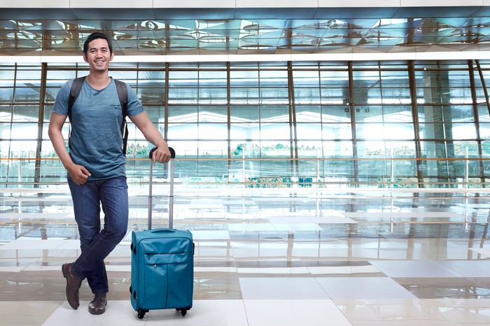 Man standing in airport with suitcase