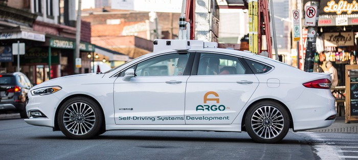 """A white Ford Fusion sedan with """"Argo AI"""" markings and visible self-driving hardware is shown on the streets in Pittsburgh."""