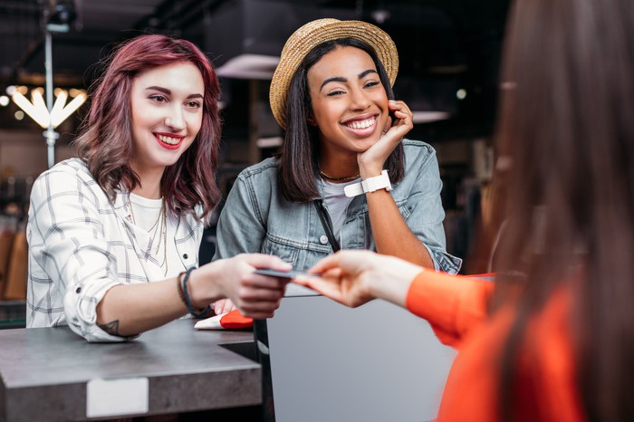 Two young women paying for purchases in a store with a credit card.