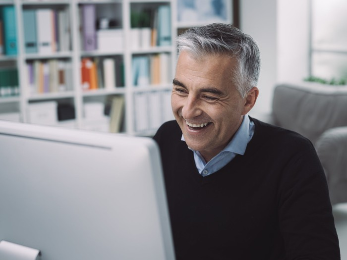 Smiling gray-haired man at laptop.