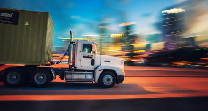 A Mobile Mini truck moving against a blurred background.