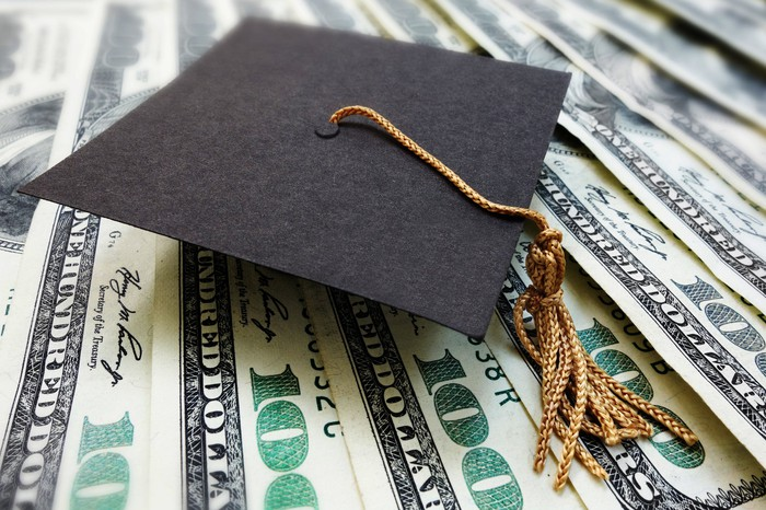 Graduation cap on a pile of hundred dollar bills.