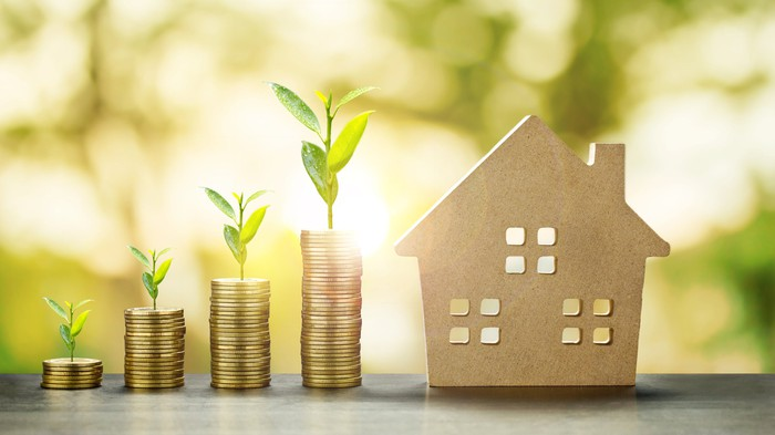 Stacked coins and a home representing rising investment returns.