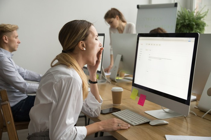 A woman sitting in front of a computer stifles a yawn.