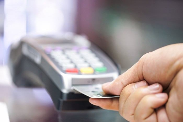 A hand inserting a credit card into a point of sale terminal.