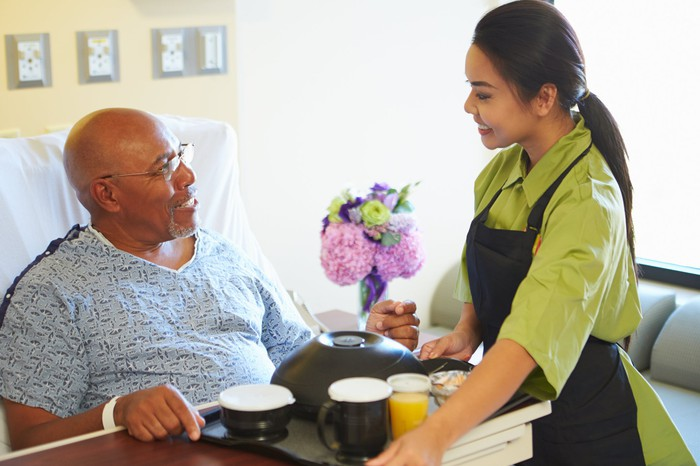 Woman wearing an apron serves a tray of food to person in a hospital bed
