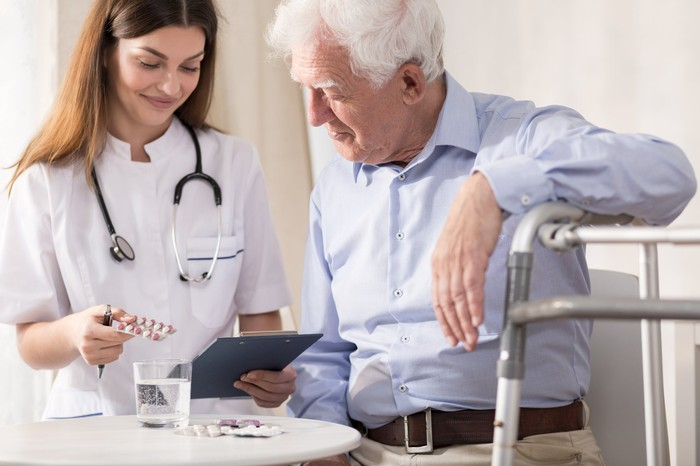 Person wearing medical scrubs and a stethoscope giving medication to senior male patient.
