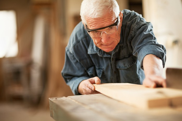 A senior man cutting a piece of wood in a wood shop.