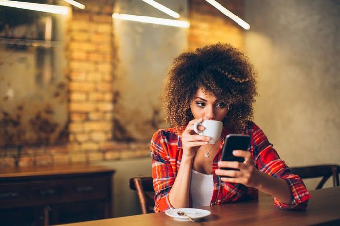 A woman drinking coffee while looking at her smartphone