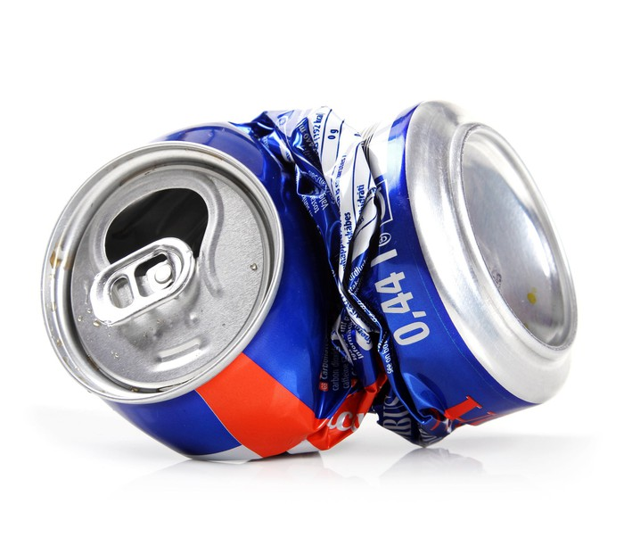 A crushed beer can in red, white, and blue against a plain white backdrop.