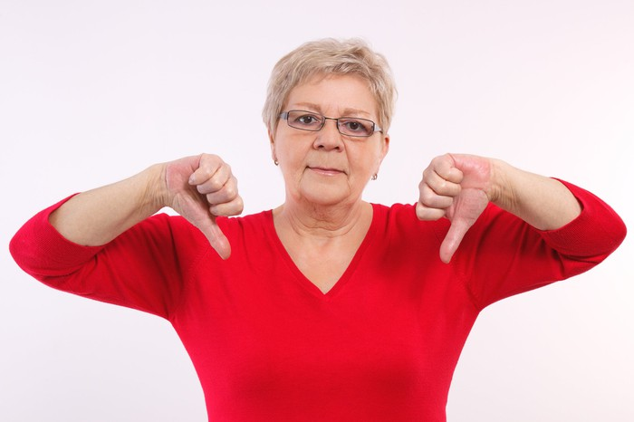 An older woman pointing her thumbs downward.