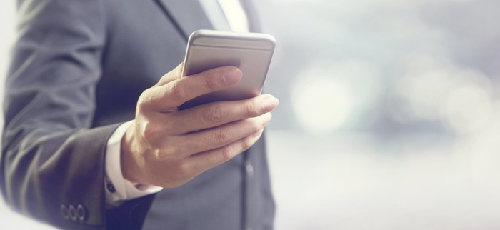 A person dressed in a suit holding a smartphone.