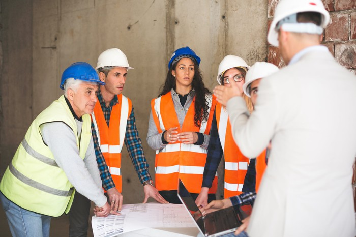 Several people with hard hats gather around a table and listen to a man also wearing a hard hat.