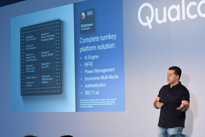 A person standing in front of a wall with a slide detailing Qualcomm's Snapdragon 850 projected onto it.
