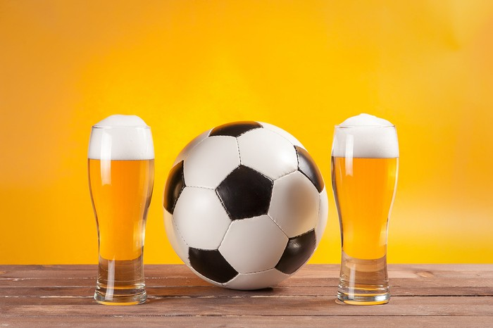 A soccer ball sits between two pints of beer.