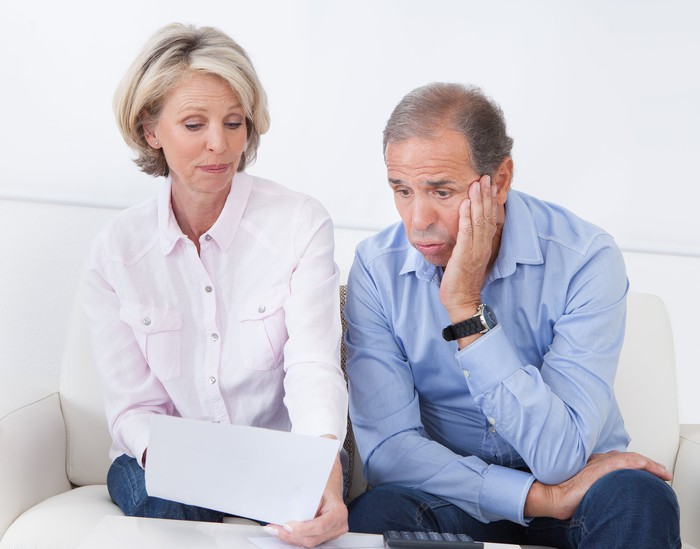 A worried senior couple review a document as they sit side by side.