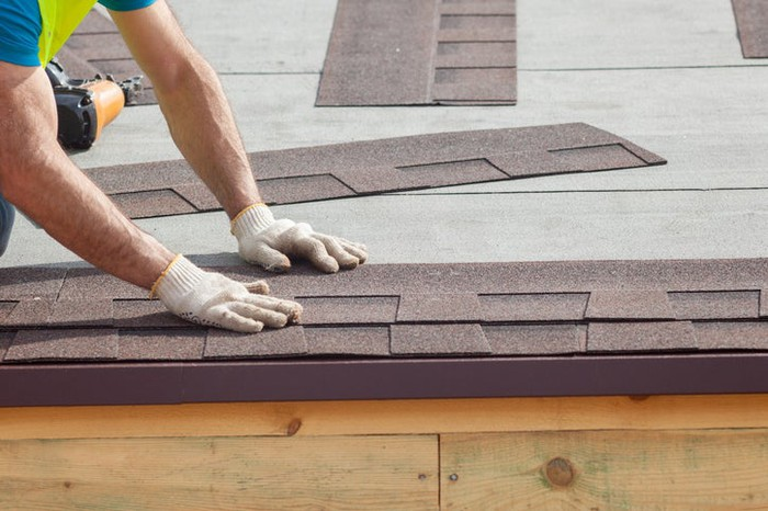 A worker installing asphalt shingles on a roof.