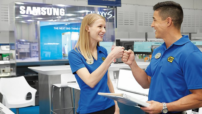 A female and male Best Buy employee smiling and giving a fist bump.