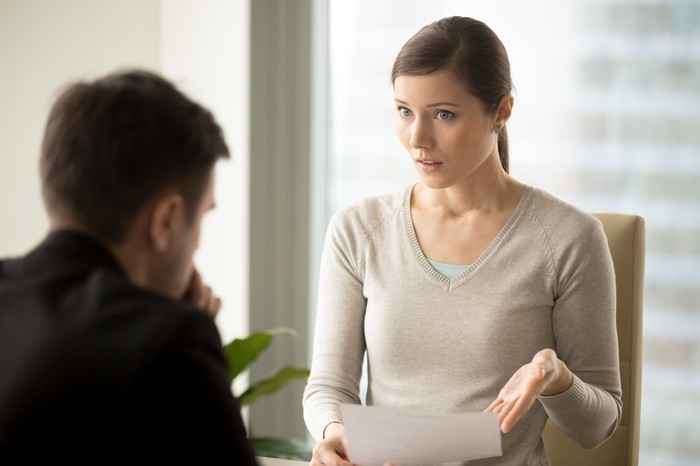 Professional woman showing professional man a document with disapproving expression.