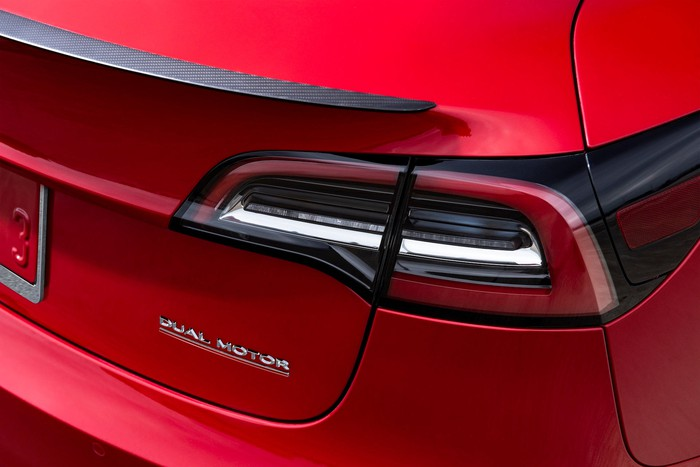 "A close-up of the ""Dual Motor"" badge on the back of a red Tesla Model 3 sedan"