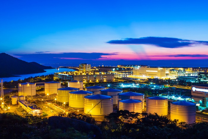 Brightly-lit oil tanks in front of a twilight sky