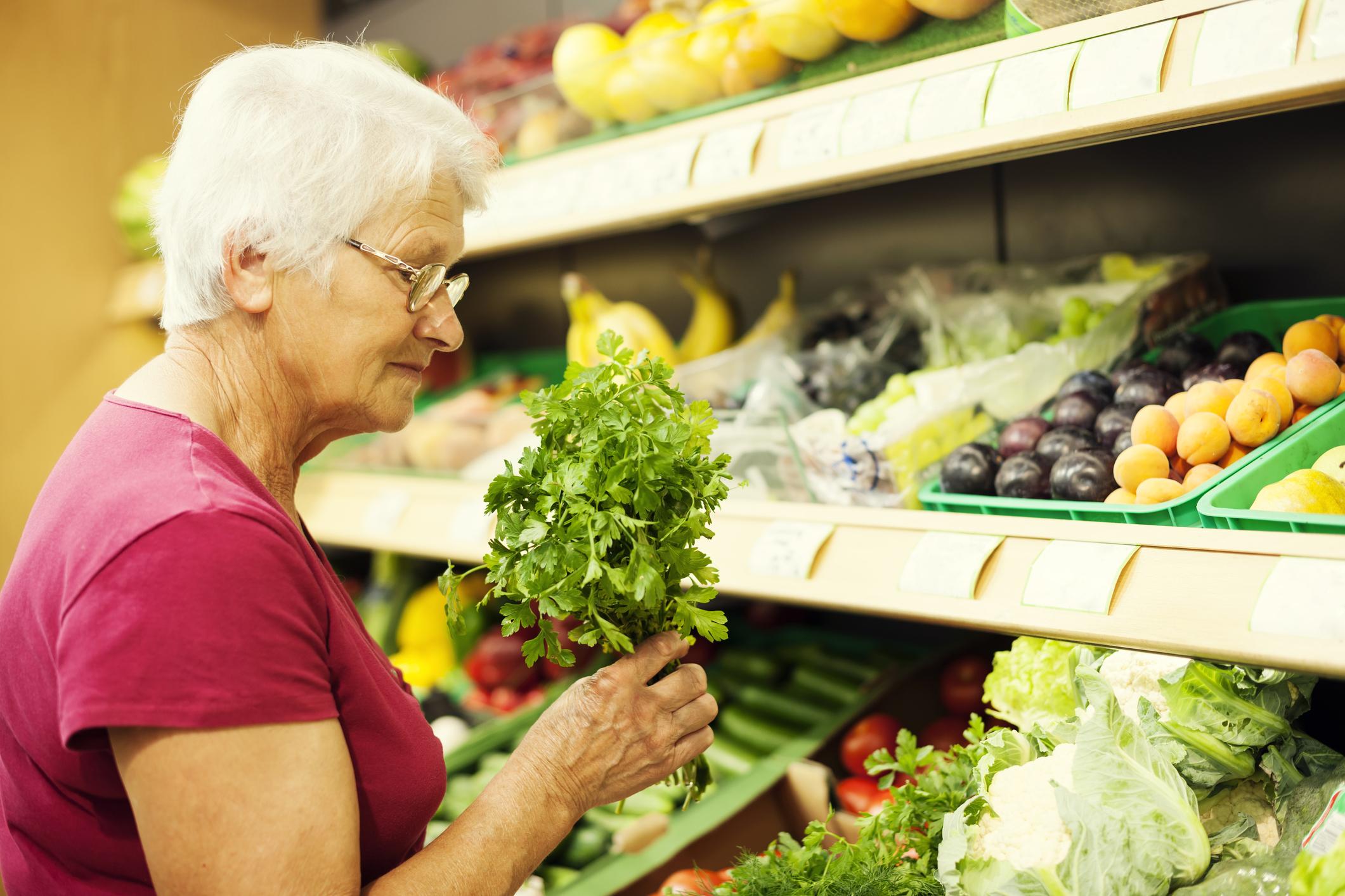 Senior woman buying produce at supermarket