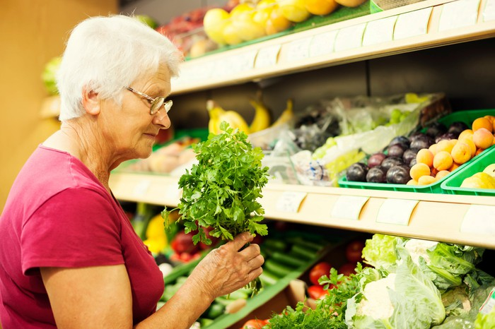 Senior woman buying produce at supermarket