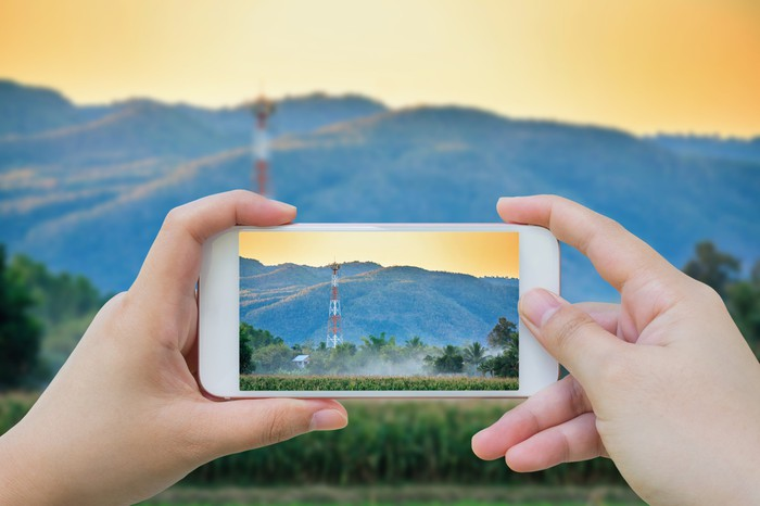 A person taking a picture of a cell tower with their mobile phone.