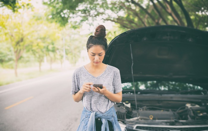 Woman standing in front of car with hood up on the side of the road