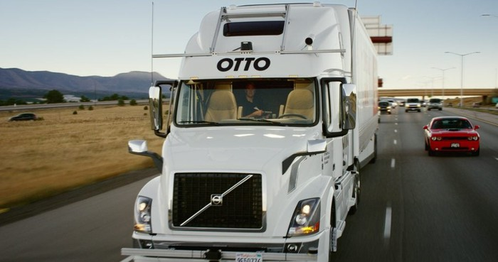 "A front view of a white Volvo tractor-trailer truck with ""OTTO"" logo and visible self-driving sensor hardware. The truck is driving on the highway, but nobody is in the driver's seat."