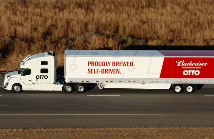 "A tractor-trailer truck on a rural road in Colorado. The white tractor has a large blue ""OTTO"" logo, whle the trailer carries Budweiser's logos in red and white."