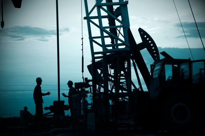 A drilling rig, silhouetted at dusk