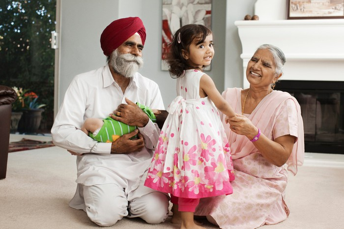 Older couple playing with small grandchildren