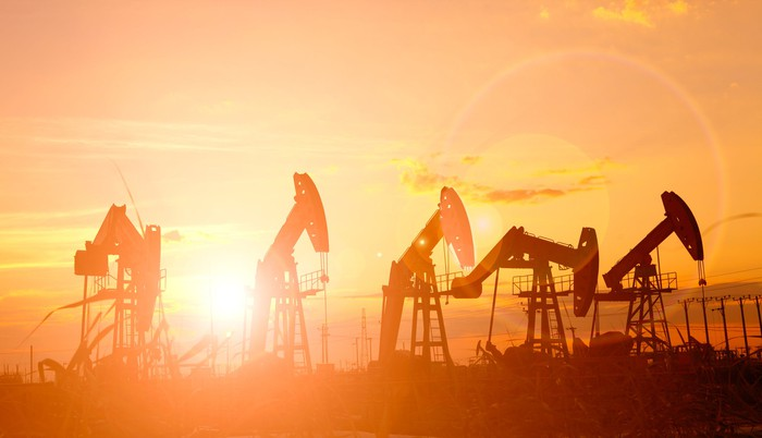 Several oil pumps with the sun shining in the background.