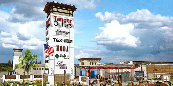 Tanger Outlets sign tower with an outlet mall in the background