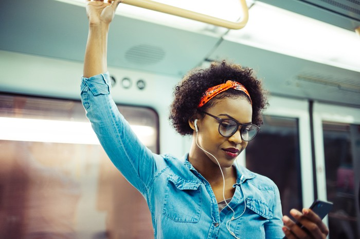 Young woman holding her smartphone listening to music on her daily commute