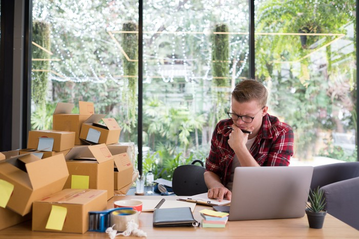 Man at laptop looking concerned with open cardboard boxes piled up next to him