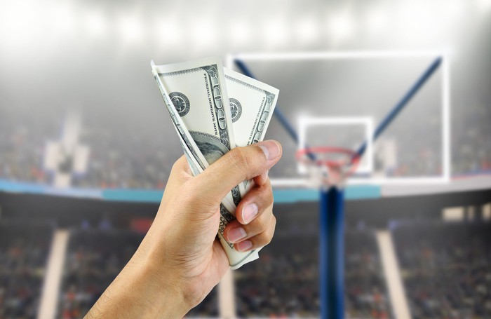 Person holding money up on basketball court.