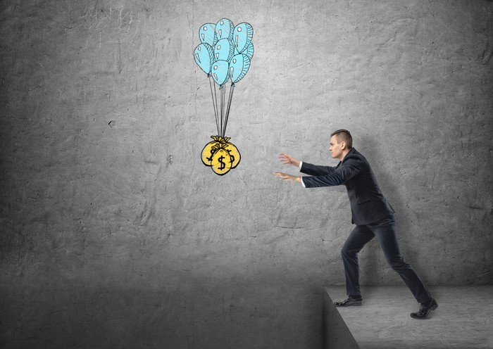 A businessman reaching over a cliff trying to grab a bag of coins at the end of a bouquet of balloons.