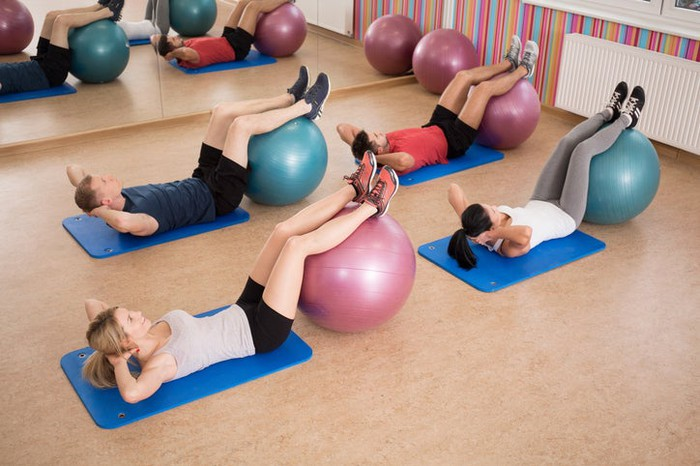 Two young women and two young men each lying on an exercise mat with hands behind head and feet on top of a large ball.