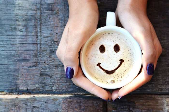 A woman holds a cappuccino with a smiley face in the foam.