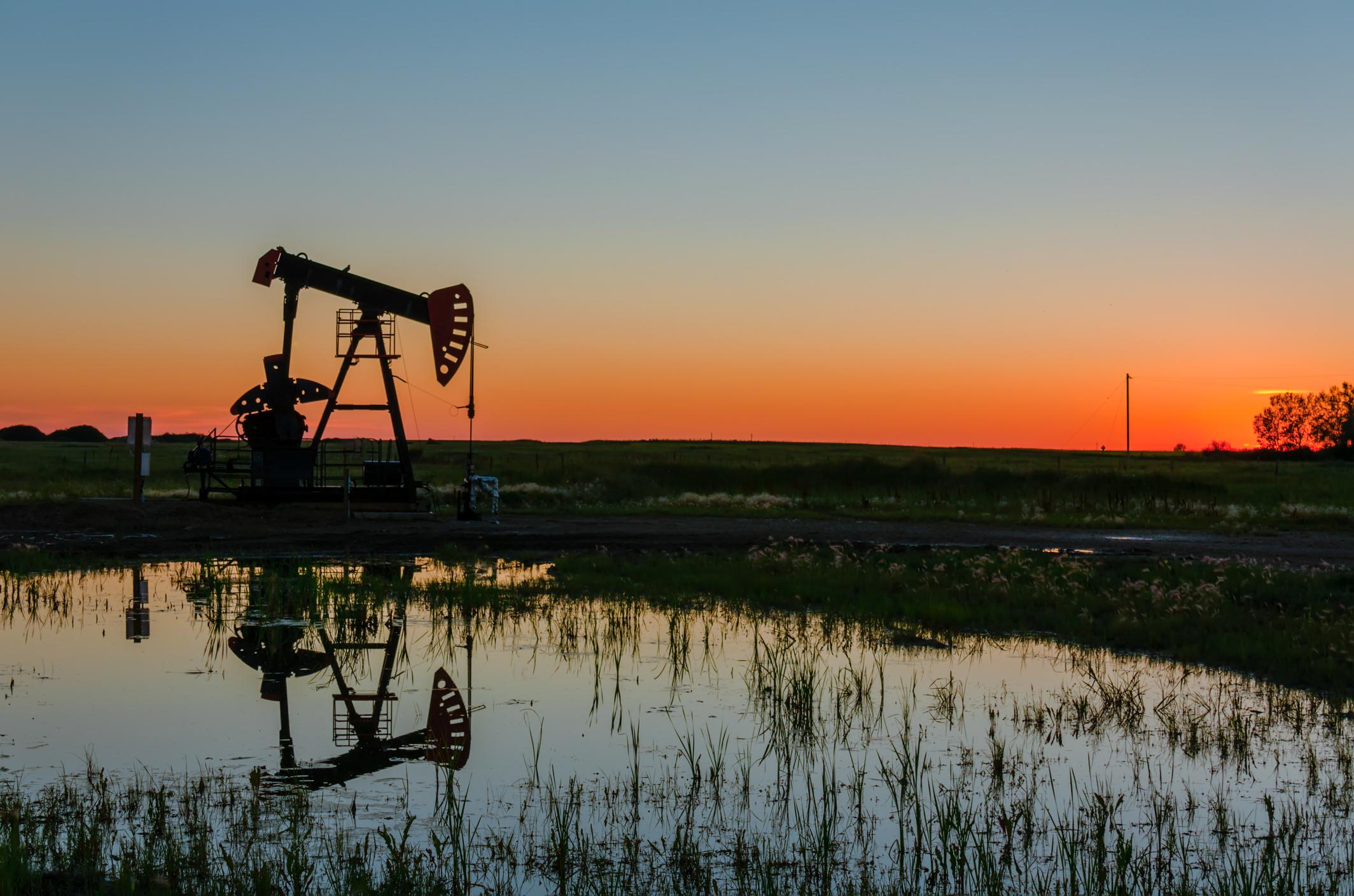 An oil pump next to a pond at sunset.
