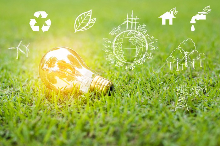 Lying on grass, a shining light bulb is surrounded by renewable energy icons.